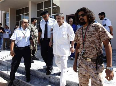 Libya's former foreign minister Abdel-Ati al-Obeidi (2nd R) leaves court after the first hearing of his trial in Tripoli September 10, 2012. REUTERS/Ismail Zitouny