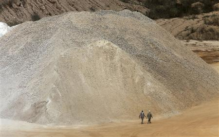 Workers walk past a pile of limestone at the Dangote Cement mine in Obajana village in Nigeria's central state of Kogi, in this November 8, 2010 file picture. REUTERS/Akintunde Akinleye/Files