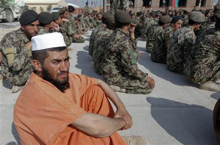 An Afghan National Army soldier, wearing a prison uniform, sits with his comrades during a ceremony handing over the Bagram prison to Afghan authorities, at the U.S. airbase in Bagram, north of Kabul September 10, 2012. Soldiers donned the prison uniforms before a media preview, which was cancelled at the last minute due to unknown reasons. REUTERS/Omar Sobhani