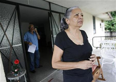 Cuban dissident Marta Beatriz Roque stands on the porch of fellow dissident's home Vladimiro Roca (rear) in Havana August 26, 2008. REUTERS/Claudia Daut