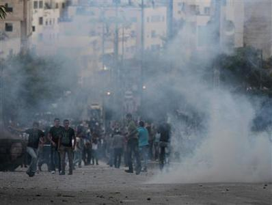 Protesters run as tear gas fired by Palestinian police rises during clashes at a demonstration against high living costs and the government in the West Bank city of Hebron September 10, 2012. REUTERS/Darren Whiteside