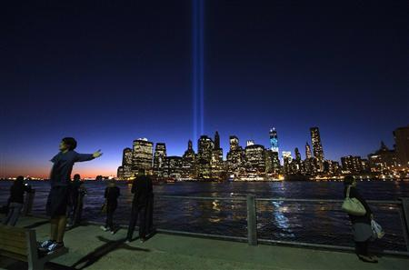 The Tribute in Light illuminates the sky over New York's lower Manhattan skyline a day ahead of the 11th anniversary of the 9/11 attacks as Natsuki, of Yokohama, Japan, raises his arms for a portrait in New York September 10, 2012. The Tribute in Light is an art installation near the site of the World Trade Center in remembrance of the September 11 attacks. REUTERS/Adrees Latif