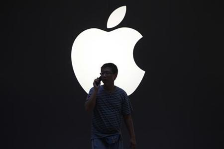 A man talks on a mobile phone in front of an Apple logo outside an Apple store in downtown Shanghai September 3, 2012. REUTERS/Aly Song