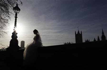 A bride sits on a wall opposite the Houses of Parliament during a wedding photo shoot in central London January 6, 2012. REUTERS/Stefan Wermuth