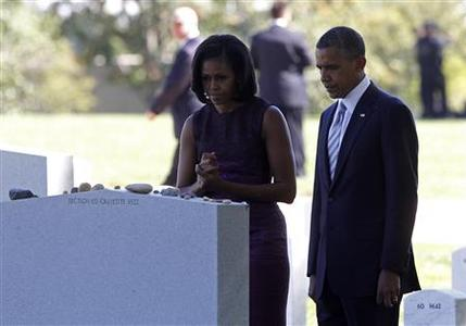 U.S. President Barack Obama and first lady Michelle Obama look at the headstone of a grave for servicemen killed in an October 26, 2009 helicopter crash in Afghanistan, during their visit to Arlington National Cemetery on the 11th anniversary of the 9/11 attacks near Washington, September 11, 2012. REUTERS/Jason Reed