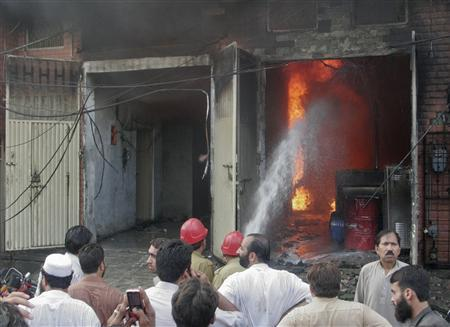 Residents gather while firefighters try to extinguish a fire at a shoe factory in Lahore September 11, 2012. REUTERS/Idrees Hussain