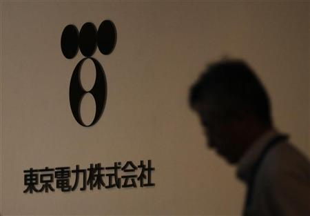 A man walks past Tokyo Electric Power Co (TEPCO)'s logo at the company headquarters in Tokyo July 30, 2012. REUTERS/Yuriko Nakao