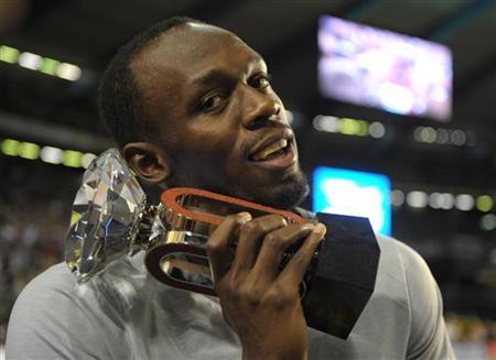Usain Bolt of Jamaica poses with his trophy after competing in the men's 100m event at the IAAF Diamond League athletics meeting, also known as Memorial Van Damme in Brussels September 7, 2012. REUTERS/Laurent Dubrule