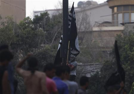 Protesters attempt to raise a Salafist flag with Arabic words that read, ''There is no God but Allah and Mohammad is his prophet'' after pulling down an American flag at the U.S. embassy in Cairo September 11, 2012. REUTERS/Amr Abdallah Dalsh