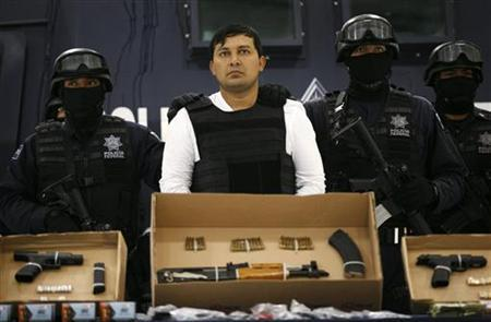 Suspect Jesus ''El Mamito'' Rejon (C) is presented by the police to the media in Mexico City July 4, 2011. REUTERS/Bernardo Montoya
