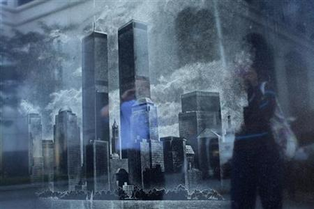 People are reflected in a Memorial Monument during events marking the 11th anniversary of the 9/11 attacks on the World Trade Center in Exchange Place in New Jersey, September 11, 2012. REUTERS/Eduardo Munoz