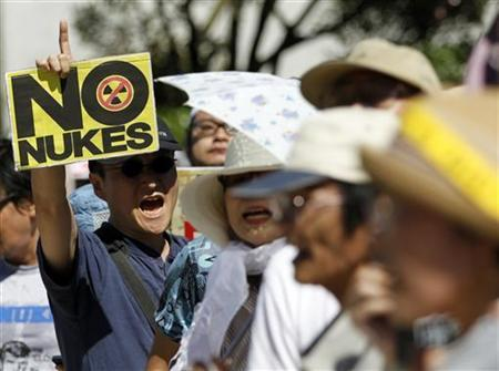An anti-nuclear protester holds a sign reading, ''No Nukes'' during a rally outside Japan's Prime Minster Yoshihiko Noda's official residence in Tokyo August 22, 2012. REUTERS/Yuriko Nakao