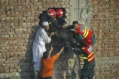 Спасатели и обычные люди вытаскивают тело из здания обувной фабрики в Лахоре после пожара, 11 сентября 2012 года. Как минимум 125 человек погибли в пожарах на фабриках в городах Карачи и Лахор в Пакистане, сообщили в среду местные власти. REUTERS/Mani Rana