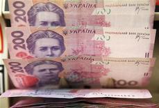 Кассир пересчитывает купюры валюты гривна в Киеве 21 февраля 2010 года. Валовый внутренний продукт Украины в 2013 году вырастет на 3,4 процента по сравнению с ростом на 3,9 процента, прогнозируемым на 2012 год, сказал премьер-министр Николай Азаров, представляя правительственный проект бюджета на следующий год. REUTERS/Konstantin Chernichkin