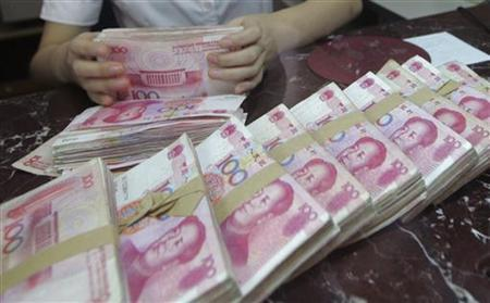 An employee counts Chinese 100 yuan banknotes at a branch of Bank of Communications in Shenyang, Liaoning province July 6, 2012. REUTERS/Stringer