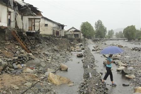 A woman holding an umbrella walks past near damaged houses by recent flooding in Kujang district, in the province of North Pyongan, August 28, 2012. REUTERS/Mission East/Handout