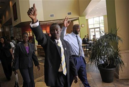 Attorney Benjamin Crump (C) waves to supporters with Tracy Martin (R) and Sabrina Fulton (L), the parents of the late Trayvon Martin, after they addressed lawmakers at a meeting on Florida's 'Stand Your Ground' law in Longwood, Florida, June 12, 2012. REUTERS/David Manning