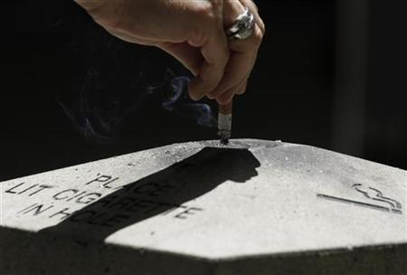 A woman disposes a cigarette in Los Angeles, California, May 31, 2012 .REUTERS/Jonathan Alcorn