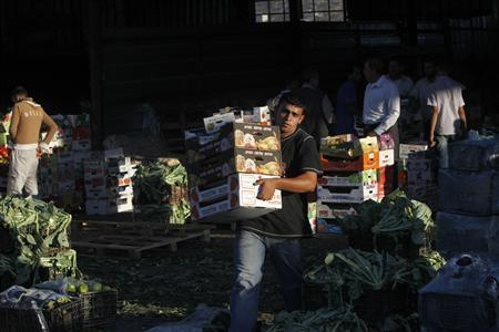 A worker carries boxes at a wholesale vegetable and fruit market in the West Bank village of Beita, near Nablus September 2, 2012. Once the mainstay of the local economy, Palestinian agriculture in the rocky West Bank is in decline, with farmers struggling to protect both their livelihoods and their lands. Deprived of water and cut off from key markets, farmers across the occupied territory can only look on with a mix of anger and envy as Israeli settlers copiously irrigate their own plantations and export at will. REUTERS/Mohamad Torokman