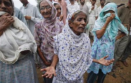 Women grieve and wait outside a building for their relatives after a fire at a garment factory in Karachi September 12, 2012. At least 261 people burnt to death as fires swept through two factories in Pakistan, police and government officials said on Wednesday, raising questions about industrial safety in the nuclear-armed South Asian nation. REUTERS/Akhtar Soomro