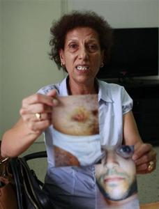 President of the Association Against Torture Radhia Nasraoui holds photographs of alleged victims of torture, during an interview with Reuters in Tunis September 11, 2012. REUTERS/Zoubeir Souissi.