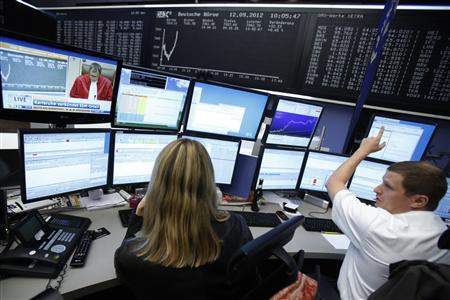 Traders react at their desks as the President of the German Constitutional Court (Bundesverfassungsgericht )Andreas Vosskuhle pronounces a judgement on the European Stability Mechanism (ESM) and fiscal pact, in front of the DAX board at the Frankfurt stock exchange September 12, 2012. Germany's Constitutional Court said on Wednesday the country can ratify the euro zone's new rescue fund and budget pact as long it can guarantee there will be no increase in German financial exposure to the bailout fund without parliament's approval. Ruling that an injunction against the ESM and fiscal compact was largely unfounded, the court said one condition for allowing ratification was that any increase in German liability beyond 190 billion euros must first be approved by the Bundestag lower house of parliament. REUTERS/Alex Domanski