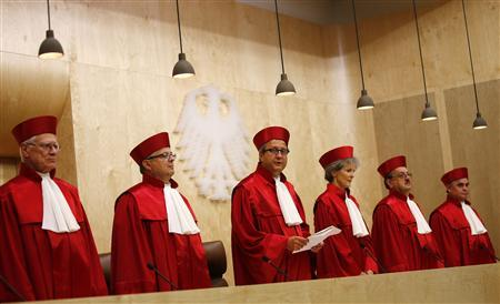 President of the German Constitutional Court (Bundesverfassungsgericht ) Andreas Vosskuhle (3rd L) stands with the other judges as he announces the ruling on the European Stability Mechanism (ESM) and the fiscal pact at the court in Karlsruhe September 12, 2012. Germany's Constitutional Court said on Wednesday the country can ratify the euro zone's new rescue fund and budget pact as long it can guarantee there will be no increase in German financial exposure to the bailout fund without parliament's approval. Ruling that an injunction against the ESM and fiscal compact was largely unfounded, the court said one condition for allowing ratification was that any increase in German liability beyond 190 billion euros must first be approved by the Bundestag lower house of parliament. REUTERS/Kai Pfaffenbach