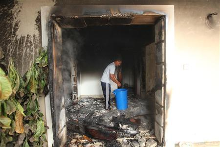 A man stands inside the U.S. consulate, which was attacked and set on fire by gunmen yesterday, in Benghazi September 12, 2012. REUTERS/Esam Al-Fetori