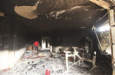 A man walks inside the U.S. consulate, which was attacked and set on fire by gunmen yesterday, in Benghazi September 12, 2012. REUTERS/Esam Al-Fetori