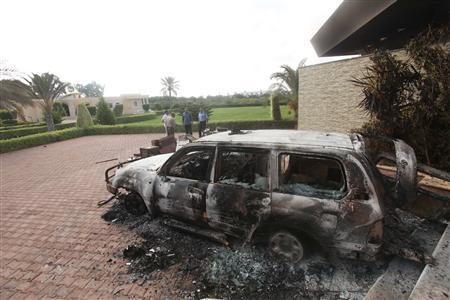 People stand near a burnt car at the U.S. consulate, which was attacked and set on fire by gunmen yesterday, in Benghazi September 12, 2012. REUTERS/Esam Al-Fetori