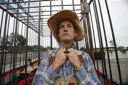 Protester David Piller, who is against Genetically Modified Organisms (GMO), is chained to a cage while blocking a delivery entrance to a Monsanto seed distribution facility in Oxnard, California September 12, 2012. REUTERS/Mario Anzuoni