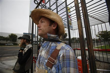 Protesters against Genetically Modified Organisms (GMO) are chained to a cage while blocking a delivery entrance to a Monsanto seed distribution facility in Oxnard, California September 12, 2012. REUTERS/Mario Anzuoni