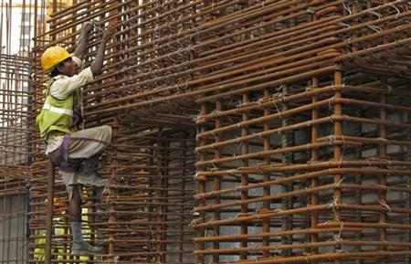 A worker climbs to fasten iron rods together at the construction site of a high-rise building in central Mumbai October 18, 2011. REUTERS/Vivek Prakash/Files