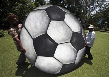 Labourers carry a plywood cut-out of a soccer ball for installation at a hotel in Chandigarh June 12, 2010. REUTERS/Ajay Verma/Files