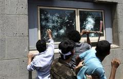 Демонстранты разбивают окна в посольстве США в Сане, 13 сентября 2012 года. Сотни демонстрантов атаковали в четверг посольство США в столице Йемена Сане в ответ на фильм о пророке Мухаммеде, и охранникам пришлось сделать несколько выстрелов в воздух, чтобы сдержать толпу. REUTERS/Mohamed al-Sayaghi