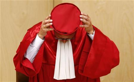 President of the German Constitutional Court (Bundesverfassungsgericht ) Andreas Vosskuhle removes his hat after announcing the ruling on the European Stability Mechanism (ESM) and the fiscal pact at the court in Karlsruhe September 12, 2012. REUTERS/Kai Pfaffenbach