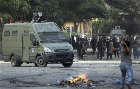 A protester throws stones towards riot policemen during clashes along a road which leads to the U.S. embassy, near Tahrir Square in Cairo September 13, 2012. REUTERS/Amr Abdallah Dalsh