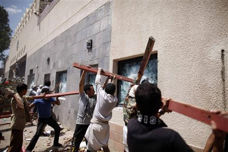 Protesters break the windows of the U.S. embassy in Sanaa September 13, 2012. REUTERS/Khaled Abdullah