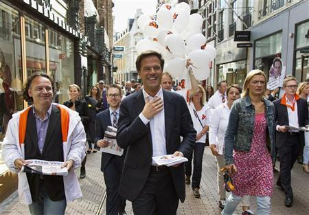 Dutch Prime Minister and Liberal Party leader Mark Rutte (C) hands out flyers in The Hague September 11, 2012. Voting begins for the Dutch general election on Wednesday. REUTERS/Michael Kooren