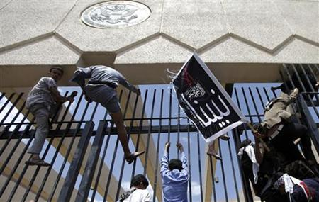 Protesters climb a fence at the U.S. embassy in Sanaa September 13, 2012. Hundreds of Yemeni demonstrators stormed the U.S. embassy in Sanaa on Thursday in protest against a film they consider blasphemous to Islam, and security guards tried to hold them off by firing into the air. Yemen's embassy in Washington said no casualties were reported when the protesters stormed the U.S. embassy compound in Sanaa on Thursday. The poster reads, 'Anything but our prophet'. REUTERS/Mohamed al-Sayaghi