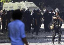 Policial anti-motim aponta arma de gás lacrimogêneo contra um manifestante durante confrontos na estrada que leva à embaixada norte-americana, no Cairo. Manifestantes atacaram as embaixadas dos EUA no Iêmen e no Egito, em novos protestos contra um filme que consideram ofensivo ao profeta Maomé. 13/09/2012 REUTERS/Amr Abdallah Dalsh
