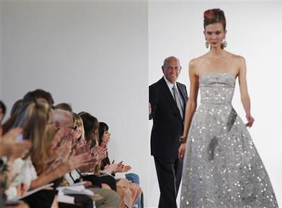 Designer Oscar De La Renta watches a model as she walks the runway during a show of his Spring/Summer 2013 collection during New York Fashion Week, September 11, 2012. REUTERS/Lucas Jackson