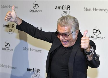 Italian stylist Roberto Cavalli gestures as he arrives at the amfAR's Milan Fashion Week Gala in Milan September 23, 2011. REUTERS/Paolo Bona
