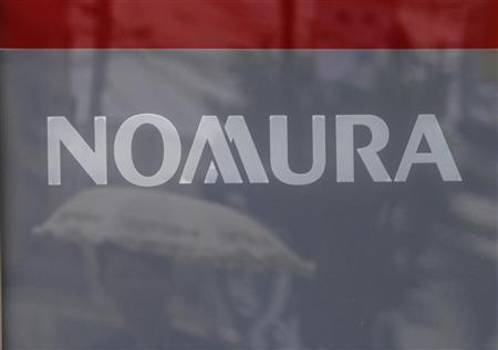 A woman under an umbrella is reflected on a sign board outside a Nomura Securities branch in Tokyo August 3, 2012. REUTERS/Yuriko Nakao