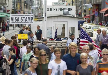 Tourists visit the former Checkpoint Charlie border crossing in Berlin, August 25, 2012. REUTERS/Thomas Peter