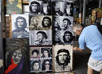 A tourist looks at paintings at an artisans fair in Havana August 24, 2012. REUTERS/Desmond Boylan