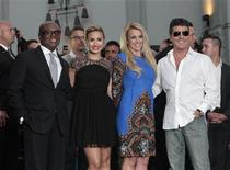 "Judges (from L-R) L.A. Reid, Demi Lovato, Britney Spears and Simon Cowell pose after leaving their handprints and signatures in cement at the season two premiere of the television series ""The X Factor"" at Grauman's Chinese theatre in Hollywood, California September 11, 2012. REUTERS/Mario Anzuoni"