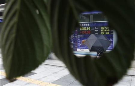 A stock quotation board is seen through a hole of a leaf outside a brokerage in Tokyo September 12, 2012. REUTERS/Toru Hanai