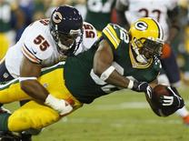 Green Bay Packers running back Cedric Benson (R) is tackled by Chicago Bears linebacker Lance Briggs in the first half during their NFL football game in Green Bay, Wisconsin September 13, 2012. REUTERS/Darren Hauck