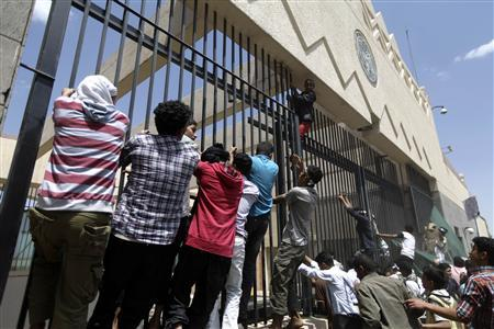 Protesters climb a fence surrounding the U.S. embassy in Sanaa September 13, 2012. REUTERS/Mohamed al-Sayaghi